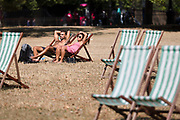 A couple sunbathe on deckchairs in St Jamess Park in London, England during the ongoing summer heatwave on August 07, 2018.