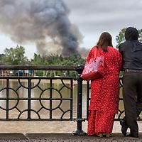 A couple looking on a big smoke cloud in Kuching.