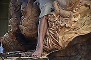 Detail of a wood sculpture and of the leg of the man who is working on it, in Sapa surroundings, Lao Cai province, North Vietnam.