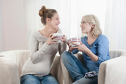 Two women drinking tee talking chair at home