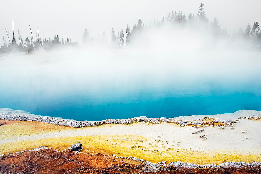 Steam rises from Abyss Pool hot spring, West Thumb Geyser Basin, Yellowstone National Park, Wyoming. The colors along the edge come from thermophilic bacteria.
