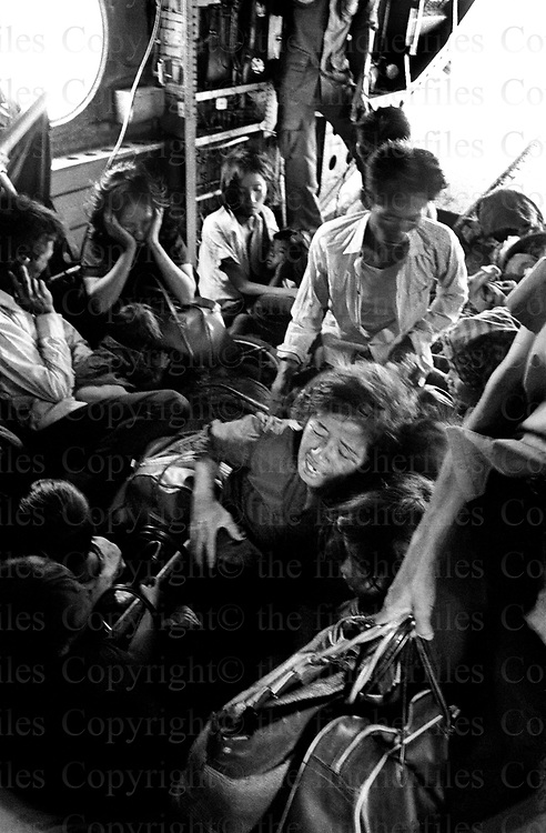 Evacuations near Xuan Loc in South Vietnam as the North Vietnamese army made their advance on the city. Distraught mother during the evacuation of Xuan Loc, Vietnam as the North Vietnamese advance. A woman is cries hysterically as she has just seen her baby fall from the back of the American rescue helicopter during the panic of refugees. Xuan Loc was the last major battle of the Vietnam War fought between 9th and 21st April 1975. Photographed by photographer Terry Fincher.
