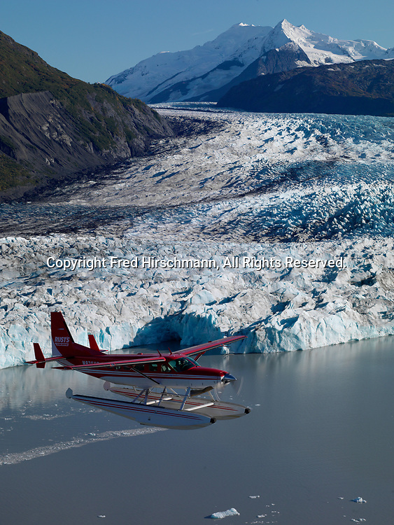 Rust's Flying Service Cessna 208 Caravan on floats flying above Colony Glacier with Mount Muir beyond, Lake George, Alaska.