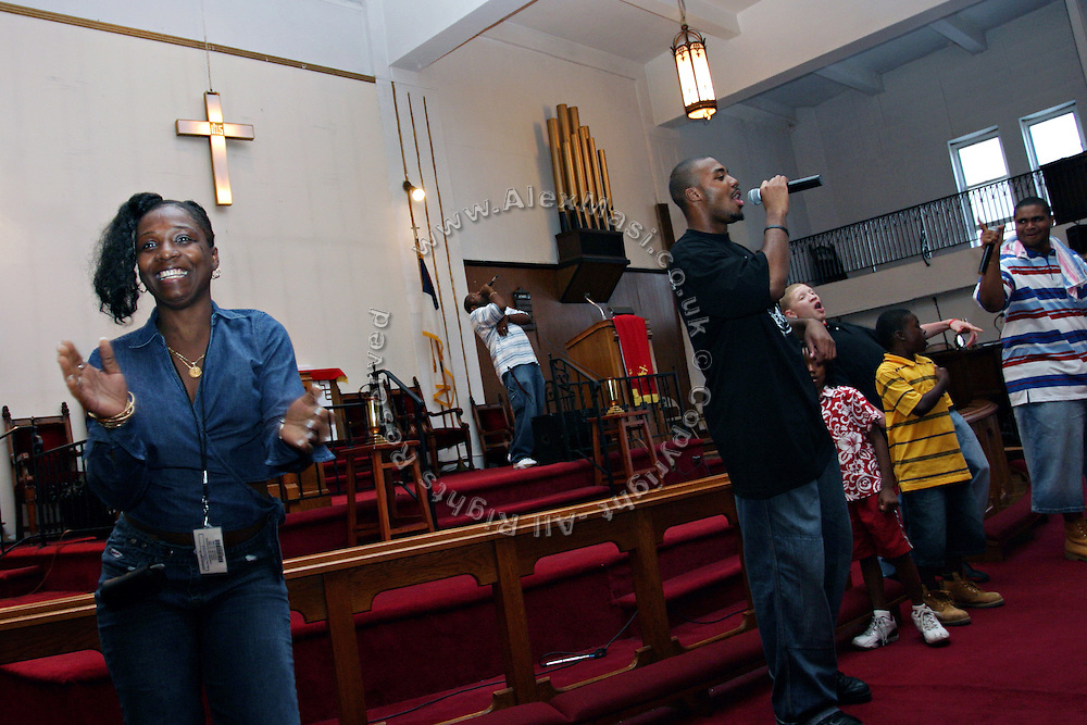 Christian woman dancing Hip Hop music while the Hells Most Wanted, a Christian Hip Hop group, are singing in the background, during a Mass Service at the Hip Hop Church in Harlem, New York, NY., on Thursday, July 6, 2006. A new growing phenomenon in the United States, and in particular in its most multiethnic city, New York, the Hip Hop Church is the meeting point between Hip Hop and Christianity, a place where ?God? is worshipped not according to religious dogmatisms and rules, but where the ?Holy Spirit? is celebrated by the community through young, unique, passionate Hip Hop lyrics. Its mission is to present the Christian Gospel in a setting that appeals to both, those individuals who are confessed Christians, as well as those who are not regularly attending traditional Services, while helping many youngsters from underprivileged neighbourhoods to feel part of a community, to make them feel loved and to help them not to give up when problems arise. The Hip Hop Church is not only forward-thinking but it also has an important impact where life at times can be difficult and deceiving, and where young people can be easily influenced for the worst purposes. At the Hip Hop Church, members are encouraged to sing, dance and express themselves in any way that the ?Spirit of God? moves them. Honours to students who have overcome adversity, community leaders, church leaders and some of the unsung pioneers of Hip Hop are common at this Church. Here, Hip Hop is the culture, while Jesus is the centre. Services are being mainly in Harlem, where many African Americans live; although the Hip Hop Church is not exclusive and people from any ethnic group are happily accepted and involved with as much enthusiasm. Rev. Ferguson, one of its pioneer founders, has developed ?Hip-Hop Homiletics?, a preaching and worship technique designed to reach the children in their language and highlight their sensibilities, while bringing forth Christianity. This ?Keep It Real? evangelism style is th