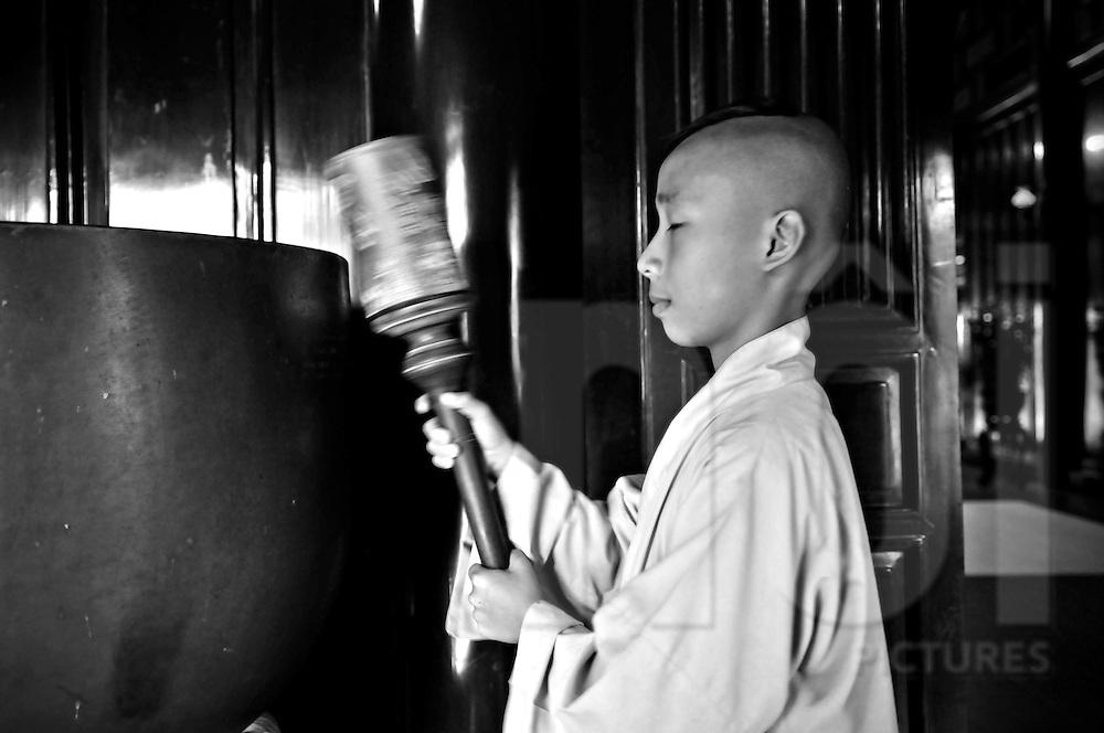 A young Vietnamese monk bangs the gong in Thien Mu pagoda, Hue, Vietnam, Southeast Asia