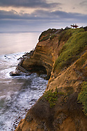 Coastal fog clouds, breaking waves, and surfers overlooking the Pacific Ocean, at Sunset Cliffs, San Diego, California