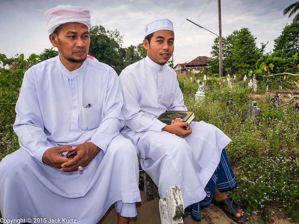 19 JUNE 2015 - PATTANI, PATTANI, THAILAND:  Men in the Muslim cemetery in Pattani. Perkuboran To'Ayah is the Muslim cemetery in Pattani. It is more than 150 years old. The last Sultan of Pattani, who ruled until Siam (Thailand) annexed Pattani is buried in the cemetery. Many victims of political and sectarian violence that has wracked Thailand's three Muslim majority provinces, Pattani, Narathiwat and Yala are also buried in the cemetery. On Fridays, after morning prayers, Muslim men come to the cemetery to tend to the graves of their family members.  PHOTO BY JACK KURTZ