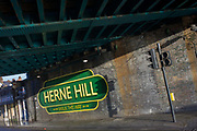 Old railway-style sign under the railway bridge in Herne Hill, South London SE24. The area grew as a result of the railways and the rail bridge overhead still handles trains travelling from the southern suburbs into central London.