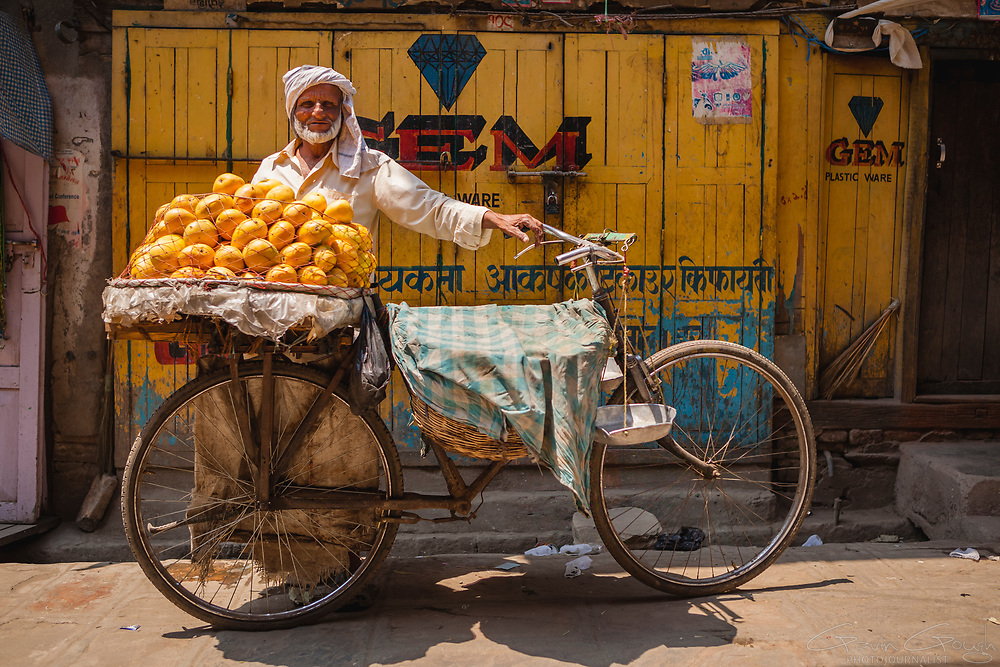A street vendor selling oranges from the rear panniers of a bicycle in the market, Asan Tole, Kathmandu, Nepal