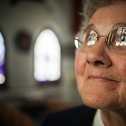 """Sister Andrea Verchuck, looks up at the stained glass inside the Immaculate Conception Chapel at the Saint Benedict Monastery, in Bristow, VA.  The Benedictine Sisters of Virginia dates back to 1868, Saint Benedict Monastery was built in 1901 and the Chapel in 1933.  Sister Andrea joined the Monastery in 1950 when she was only 15.  She says about her decision to become a nun at such an early age, """"I think the most rewarding thing was an assurance that this is what I was meant to do.  I have had more happiness and more satisfaction and more fulfillment in this than in anything I think I could do."""" John Boal Photography"""