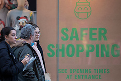 © Licensed to London News Pictures. 05/12/2020. Manchester, UK. Shoppers walk past a Safer Shopping sign on a  busy Market Street in Manchester as people try to fit in Christmas shopping. Non-essential retail is open in Manchester which is in Tier 3 restrictions. Photo credit: Kerry Elsworth/LNP
