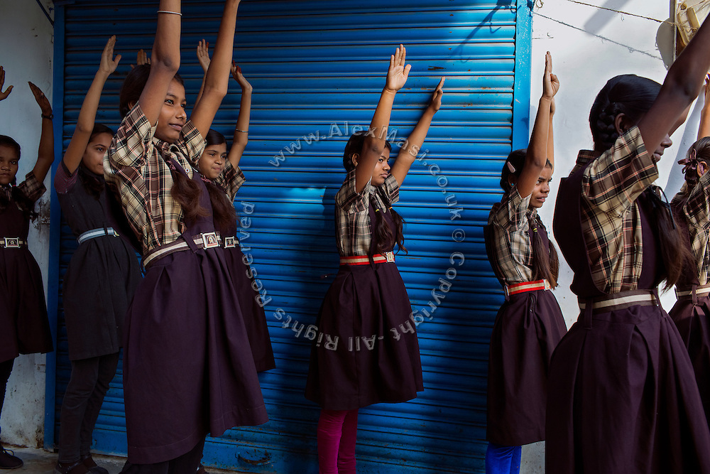 Before starting lessons in the morning, Poonam, 13, (centre) and her older sister Jyoti, 14, (next right) are exercising alongside other pupils in front of the cozy, private school they regularly attend since 2011, located close to their newly built home in Oriya Basti, one of the water-contaminated colonies in Bhopal, central India, near the abandoned Union Carbide (now DOW Chemical) industrial complex, site of the infamous '1984 Gas Disaster'. The two girls are studying in Year 6, out of 12, in 2015-16.