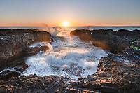 Waves crash though lava headlands during sunet at Cape Perpetua Oregon