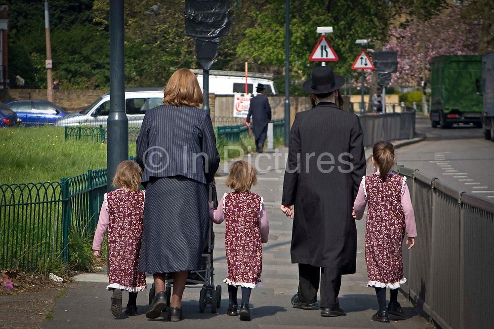 An orthodox Jewish family walk on the pavement of a busy road in Stamford Hill, London, England, United Kingdom.  Stamford Hill area is home to one of the largest populations of Orthodox Jewish people.