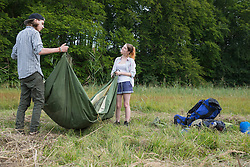 Young couple packing up their tent, Bavaria, Germany