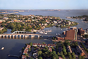 Hampton, Virginia on the James River May 2000. Norfolk & Virginia Beach are in the distance across Hampton Roads (James River) exit to the Chesapeake Bay & Atlantic Ocean. An outbound ship is crossing the channel at the I-64  Bridge Tunnel at center. Hampton University is at center between the foreground river and the larger body of water in the distance..