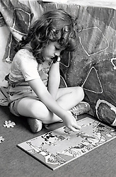 Small girl doing a jigsaw at primary school, Nottingham UK 1982