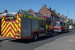 © Licensed to London News Pictures. 25/04/2020. London, UK. Two London Fire Brigade fire engines parked opposite the scene of a fatal house fire. A man has died in a house fire in Earlsfield, Wandsworth. Firefighters found the man in a ground floor bedroom. He was brought out of the property by fire crews but he died at the scene. London Fire Brigade was called at 07:36 BST and the fire was under control by 08:33 BST. Photo credit: Peter Manning/LNP