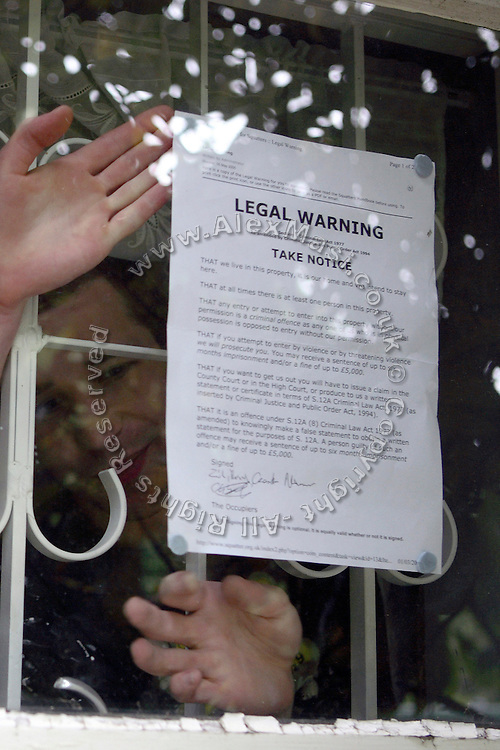 Zil, 23, from Poland is affixing the Legal Warning used by squatters as a legal way to occupy a residence left empty on the window of the mansion in Wildwood Road on Saturday, June 23, 2007, in Hampstead, London, England. Situated opposite Hampstead Heath, North London's green jewel the average price for properties on this road reaches £ 2,500,000. Million Dollar Squatters is a documentary project in the lives of a peculiar group of squatters residing in three multi-million mansions in one of the classiest residential neighbourhoods of London, Hampstead Garden. The squatters' enthusiasm, their constant efforts to look after what has become their home, their ingenuity and adventurous spirit have all inspired me throughout the days and nights spent at their side. Between the fantasy world of exclusive Britain and the reality of squatting in London, I have been a witness to their unique story. While more than 100.000 properties in London still lay empty to this day, squatting provides a valid, and lawful alternative to paying Europe's most expensive rent prices, as well as offering the challenge of an adventurous lifestyle in the capital.