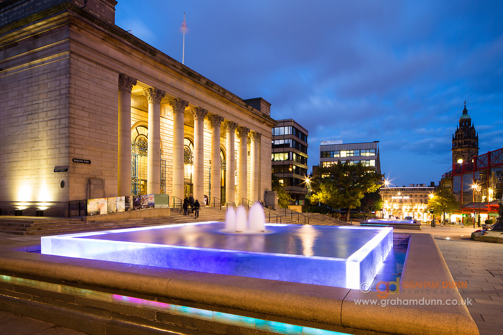 Early evening at a colourfully lit Barker's Pool in Sheffield. Balancing old and new, this square features the City Hall and two square glass-cased fountains. The Town Hall's clock tower can be seen to the right of the image. Urban landscape photography in South Yorkshire, England, UK.
