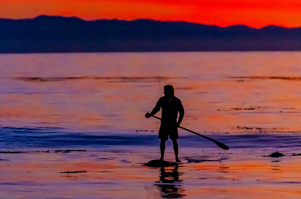 Man paddleboarding in the Pacific Ocean at sunset off Hendry's Beach (Arroyo Burro County Beach Park), Channels Islands in background, Santa Barbara, California USA.