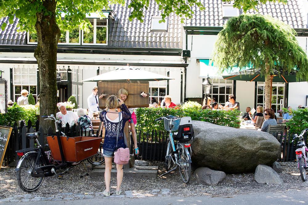 In Lage Vuursche zet een gezin de fietsen neer bij een restaurant.<br /> <br /> In Lage Vuursche a family parks their bikes near a restaurant.