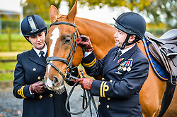 Royal Navy Lieutenants Deni Milner, left and Gary Smith fit poppies on to the bridal of Zabor at the Royal Navy and Royal Marines Riding Stables at Bickleigh Barracks, Plymouth, during the first ever memorial service dedicated to horses killed or injured in conflict.