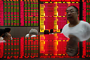 A stock display is reflected on a tabletop while investors monitor and trade stocks at a securities exchange house in Shanghai, China, on 17 August, 2010.  Despite the country's robust economy, China's stock market has not been kind to the ordinary investors, it is one of the worst performing major markets in recent years.