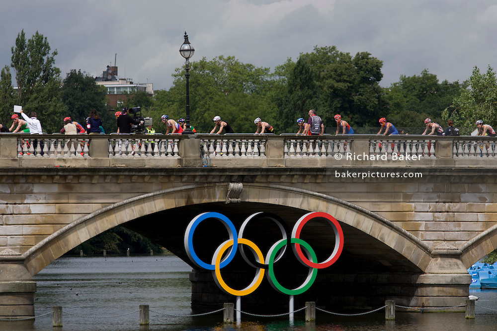 Triathletes cycle over Serpentine Bridge in London's Hyde Park for the Mens' Triathlon competition during the London 2012 Olympics, the 30th Olympiad. Serpentine Bridge marks the boundary between Hyde Park and Kensington Gardens. The Triathlon competitors raced over a 1.5km swim, a 43km bike race and a 10km run - eventually won by Team GB's Alistair Brownlee, Spain's Javier Gomez and Jonathan Brownlee (brother of the winner). The Serpentine (also known as the Serpentine River) is a 28-acre (11 ha) recreational lake in Hyde Park, London, England, created in 1730. The venue was the Hyde Park 142 hectares (350 acres) Hyde Park in the heart of the capital, one of the largest parks in central London and the site of the Victorian Great Exhibition of 1851.