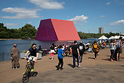 Art installation The Mastaba, by artist Christo, installed on the Serpentine lake in Hyde Park on June 18th 2018 in London, United Kingdom. The sculpture consists of 7,506 stacked barrels, painted in shades of red, white, blue and mauve. The completed piece forms part of an exhibition by Christo and his late wife, Jeanne-Claudes work, entitled Christo and Jeanne-Claude: Barrels and The Mastaba 19582018 to be held at The Serpentine Gallery.