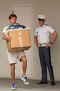 An incoming Citadel freshman known as a knob carries his newly issued gear watched by upperclassmen during matriculation day on August 17, 2013 in Charleston, South Carolina. The Citadel is a state military college that began in 1843.