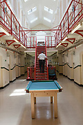 A prison guard walks through one of the residential wings at HMP Kingston. The stairs and rails are painted red. Kingston prison is a category C prison holding indeterminate sentenced prisoners. Portsmouth, United Kingdom.