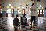 """24 SEPTEMBER 2009 -- PATTANI, THAILAND: Men pray in the Central Mosque in Pattani, Thailand. Thailand's three southern most provinces; Yala, Pattani and Narathiwat are often called """"restive"""" and a decades long Muslim insurgency has gained traction recently. Nearly 4,000 people have been killed since 2004. The three southern provinces are under emergency control and there are more than 60,000 Thai military, police and paramilitary militia forces trying to keep the peace battling insurgents who favor car bombs and assassination.  PHOTO BY JACK KURTZ"""