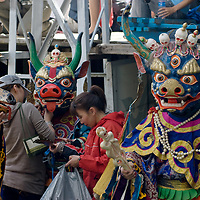 Buddhist Tsam dancers wait to perform at the national naadam festival in Ulaanbaatar, Mongolia.  Masks include (L to R): Buga, the deer; Makhi, the bull; and their master, Tshoijoo, God of the Dead and Defender of the Faith (called Yama in Sanskrit).