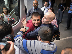 © Licensed to London News Pictures. 17/10/2016. Croydon, UK. 16 year old Afghanistani refugee 'Haris' is held back by an immigration official as he tries to reach out to his uncle Jan Ghazi, as the first children from the Calais jungle refugee camp leave the Home Office immigration centre in Croydon. British authorities are bringing over about 100 children this week to be reunited with their relatives. The French government have announced that they will be dismantling the camp this month. credit: Peter Macdiarmid/LNP