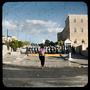 A teenage girl confronting the riot police that protects the Greek parliament.<br /> <br /> Following the murder of a 15 year old boy, Alexandros Grigoropoulos, by a policeman on 6 December 2008 widespread riots, protests and unrest followed lasting for several weeks and spreading beyond the capital and even overseas<br /> <br /> When I walked in the streets of my town the day after the riots I instantly forgot the image I had about Athens, that of a bustling, peaceful, energetic metropolis and in my mind came the old photographs from WWII, the civil war and the students uprising against the dictatorship. <br /> <br /> Thus I decided not to turn my digital camera straight to the destroyed buildings but to photograph through an old camera that worked as a filter, a barrier between me and the city.