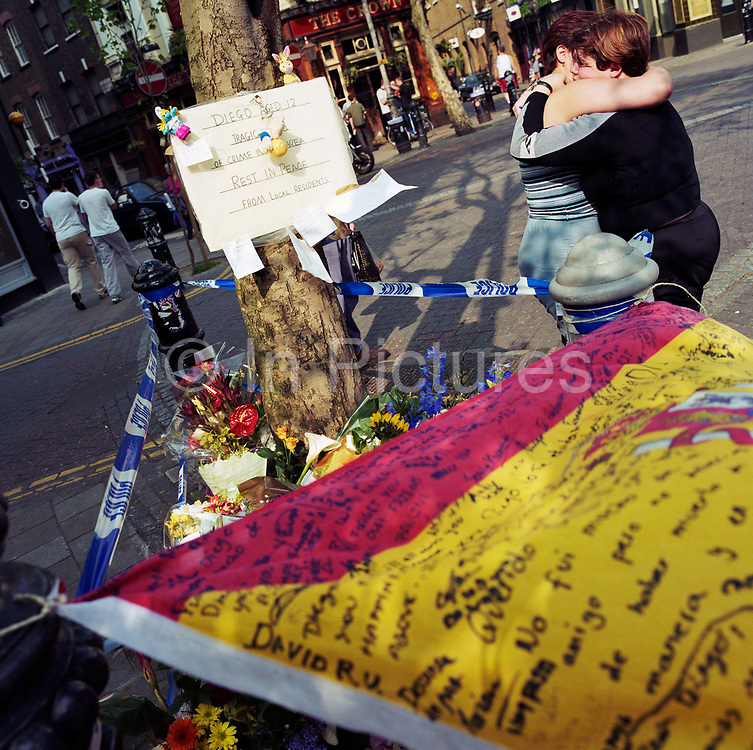 """A memorial has been placed where a young Spanish schoolboy boy called 'Diego' died at Seven Dials, Covent Garden, London, England, UK. If we drove past this place where someone's life ended, the victim would just be an anonymous statistic but flowers are left to die too and touching poems and dedications are written by family and loved-ones. One reads: """"""""Diego our friend, we are sorry you had to die like this."""" """"School will never be the same without you."""" From a project about makeshift shrines: """"Britons have long installed memorials in the landscape: Statues and monuments to war heroes, Princesses and the socially privileged. But nowadays we lay wreaths to those who die suddenly - ordinary folk killed as pedestrians, as drivers or by alcohol, all celebrated on our roadsides and in cities with simple, haunting roadside remberences."""