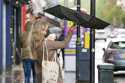 © Licensed to London News Pictures. 10/05/2021. London, UK. A woman struggles to hold an umbrella on a windy and wet morning in north London. More rain is forecast for the South East of England this week. Photo credit: Dinendra Haria/LNP