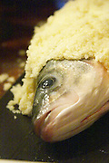How to prepare fish baked in the oven in salt crust (en croute de sel), recipe, series of pictures: head of fish in close up being covered with salt Clos des Iles Le Brusc Six Fours Cote d'Azur Var France