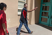 Patrick Arite points out areas of interest to a group prospective students while giving a campus tour on Thursday June 2, 2016. Arite and Nezzersare (not pictured) are both students at the University of New Mexico and are working 15-30 hours per week giving campus tours in order to help put themselves through college. (Steven St. John for NPR)