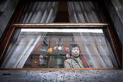 Una donna asiatica osserva dalla finestra quello che accade in strada, 12 ottobre 2012.<br /> Foto OneShot/Christian Mantuano