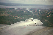 Aerial view over port wing from Dakota 4-engine DC6 plane approaching city of Manaus, Brazil 1962