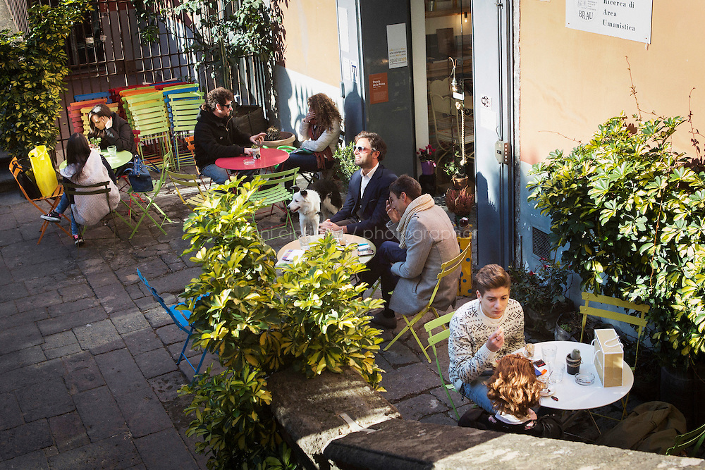 """NAPLES, ITALY - 12 DECEMBER 2014: Customers sit in the terrace of Nea, a cafè  and art gallery that is part of the """"Rete del Caffè Sospeso"""" (Suspended Coffee Network) in Naples, Italy, on December 12th 2014.<br /> <br /> A caffè sospeso,or suspended coffee, is a cup of coffee paid for in advance as an anonymous act of charity. The tradition began in the working-class cafés of Naples, where someone would order a sospeso, paying the price of two coffees but receiving and consuming only one. A poor person enquiring later whether there was a sospeso available would then be served a coffee for free."""