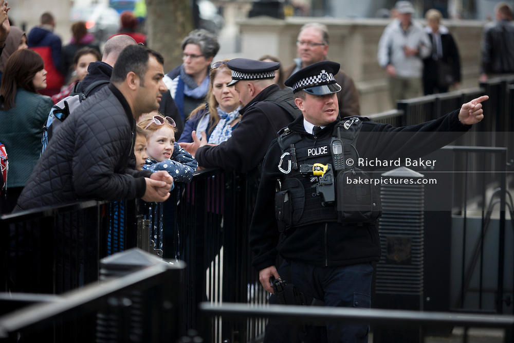 Diplomatic protection police officer interacting with tourists at the gates of Downing Street, the Prime Minister's address in Westminster London.