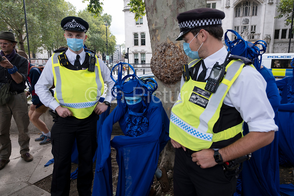 Extinction Rebellion activists Blue Rebels perform while the police in face masks look on at the Marine Rebellion march on 6th September 2020 in London, United Kingdom. Ocean Rebellion, Sea Life Extinction, Animal Rebellion and Extinction Rebellion joined together to celebrate the biodiversity found in our seas, and to grieve at the destruction of the Earth's oceans and marine life due to climate breakdown and human interference, and the loss of lives, homes and livelihoods from rising sea levels. Extinction Rebellion is a climate change group started in 2018 and has gained a huge following of people committed to peaceful protests. These protests are highlighting that the government is not doing enough to avoid catastrophic climate change and to demand the government take radical action to save the planet.