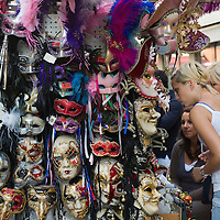 VENICE, ITALY - AUGUST 11:  Two tourists look at masks at a stall near Rialto Bridge on August 11, 2011 in Venice, Italy. Italian heritage group Italia Nostra warned  that Venice is facing an irreversible environmental catastrophe unless visitor numbers are capped. The acceptable maximum number of tourists for Venice is 33,000. In 2011 the average number of visitors to the city daily is 60,000 that is too high for such a fragile city and is causing the gradual destruction of the lagoon ecosystem.