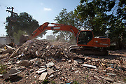 A digging taking apart and collecting rubble from the last homes on the site - Vila Autodromo favela, in the west zone of Rio, is in direct site of the Rio 2016 Olympic park. There has been an ongoing struggle between residents and the City Government of Eduardo Paes. After a long battle, 20 families who held on were allowed to stay, on the provision that they moved into houses constructed by the state, in the same style as the public housing programme.