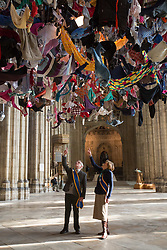 "@Licensed to London News Pictures 22/02/2018. Canterbury, UK. The cathedral ""Welcomers"", Cyril Whitehead and Alison Bowman prepare to view artist Arabella Dorman installation called ""Suspended"" which opens to the public tomorrow 23rd February 2018 in the nave of Canterbury Cathedral in Kent. This evocative artwork highlights the plight of refugees around the world and is made up of hundreds of items of refugee clothing found mainly on the beaches of the Greek Island of Lesbos. Photo credit: Manu Palomeque/LNP"