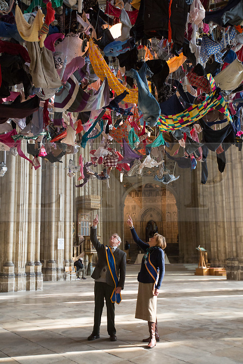 """@Licensed to London News Pictures 22/02/2018. Canterbury, UK. The cathedral """"Welcomers"""", Cyril Whitehead and Alison Bowman prepare to view artist Arabella Dorman installation called """"Suspended"""" which opens to the public tomorrow 23rd February 2018 in the nave of Canterbury Cathedral in Kent. This evocative artwork highlights the plight of refugees around the world and is made up of hundreds of items of refugee clothing found mainly on the beaches of the Greek Island of Lesbos. Photo credit: Manu Palomeque/LNP"""