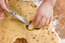 Human hand cutting dough with knife for cookies, close up